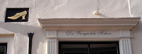 Naam en gevelsteen in pand <em>De Vergulde Schoe</em> aan de Sint-Janstraat in Middelburg (2010).