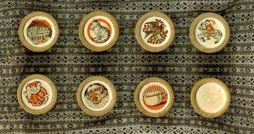 Acht van de 21 verschillende speelstukken of doppen van slabberjan, op een zakje van boerenbont : Jan Rit, Herberg, Smoel, Poesje, Pispot, Vogel, Wittebrood en Kap-a