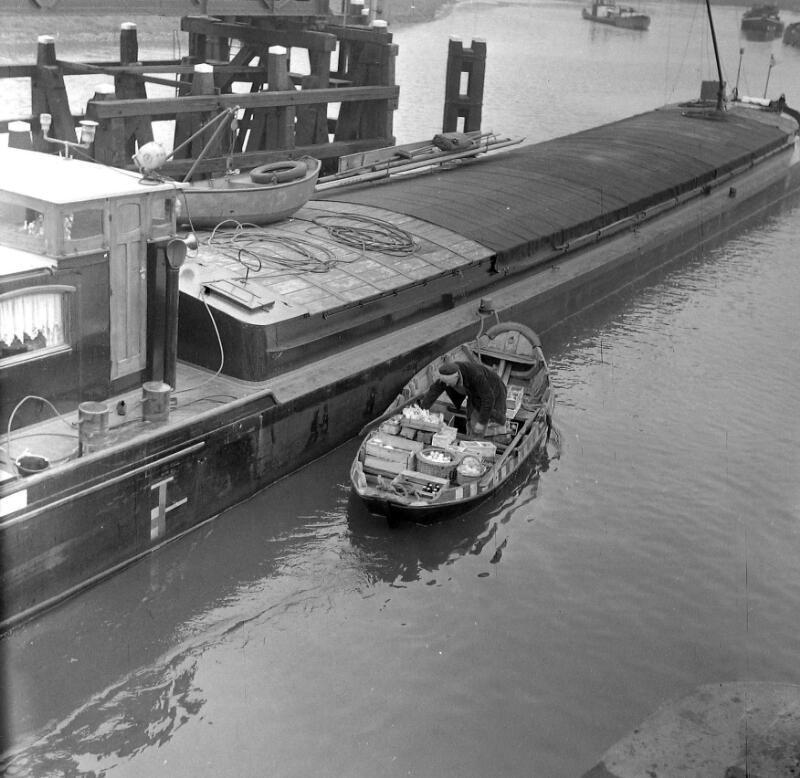 Een parlevinker levert met zijn roeiboot de bestelling van een schipper af, circa 1958. (ZB, Beeldbank Zeeland)