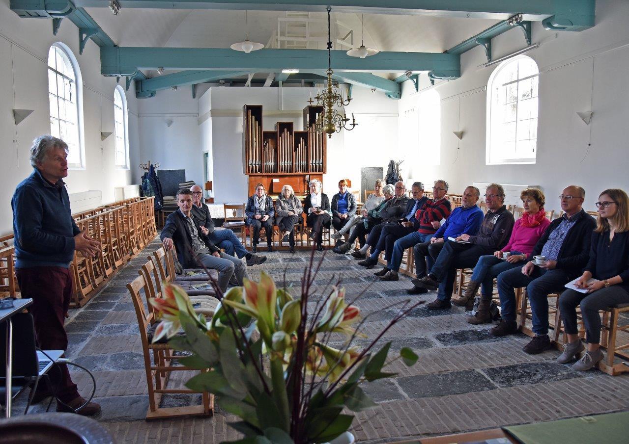 Dominee Derk Blom vertelt over de geschiedenis van 't kerkje in Waterlandkerkje (Foto door Peter Nicolai)