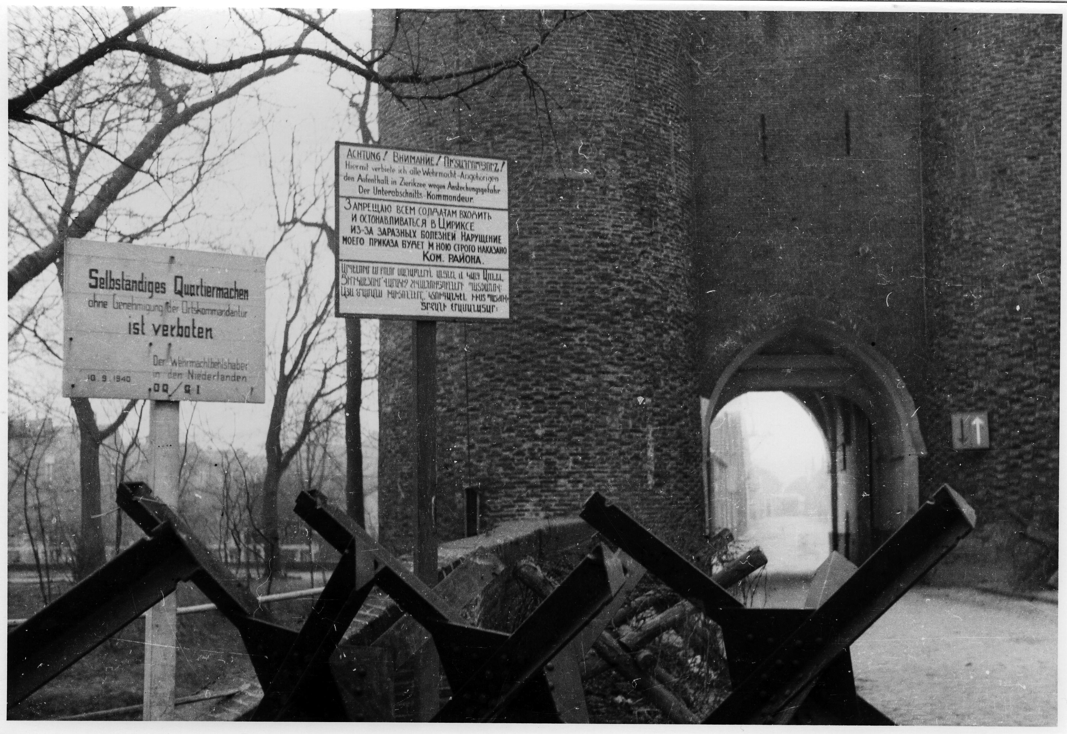 Op deze foto wordt een bord getoond bij de Nobelpoort in Zierikzee waarop de toegang tot de stad wordt ontzegd vanwege het besmettingsgevaar met difterie. De boodschap is in het Duits, Russisch én Armeens. (Bron: Museumhaven Zeeland)