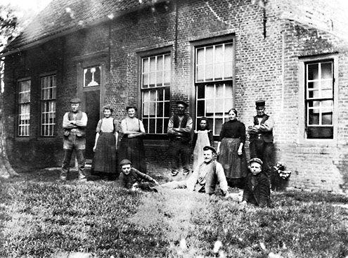 Boerenfamilie met knechten en meiden in West-Zeeuws-Vlaanderen, circa 1935. (Zeeuwse Bibliotheek, Beeldbank Zeeland)