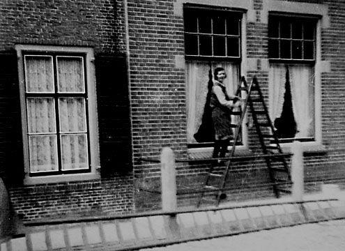 Dienstmeisje lapt de ramen van het huis van de heer Geluk in de Voorstraat in Sint-Annaland, circa 1938. (Foto M. van der Weele. Zeeuwse Bibliotheek, Beeldbank Zeeland)