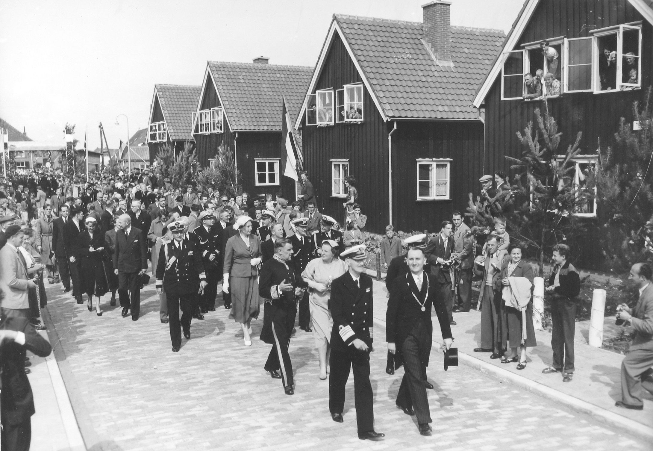 In gezelschap van koningin Juliana bracht de Noorse koning Haakon op 13 augustus 1954 een bezoek aan Stavenisse. Op de achtergrond de door Noorwegen geschonken prefabwoningen in de Koning Haakonstraat. (Zeeuwse Bibliotheek, Beeldbank Zeeland)