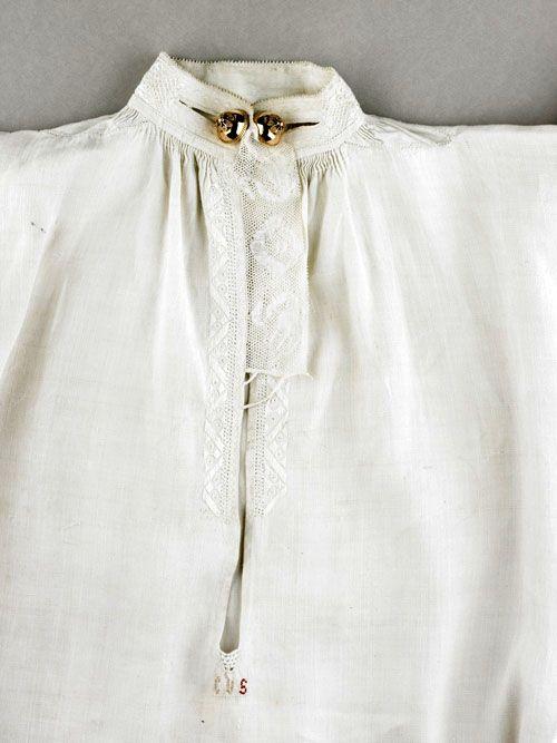 Detail van een mannenhemd met geborduurd halsboord en keelknopen, 1775-1800. Linnen, kloskant, zijde, goud. Collectie Zeeuws Museum, foto Ivo Wennekes.