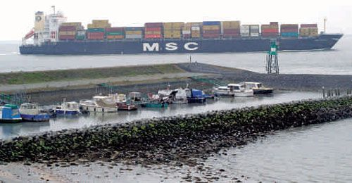 Het haventje van De Griete met een containerschip op de Westerschelde.