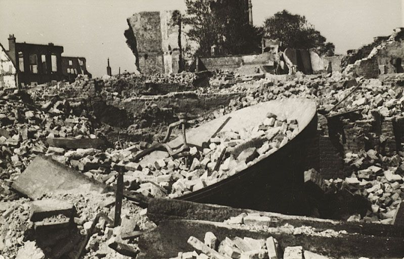 De uit de toren van de Abdij gevallen grote klok in de puinhopen in het centrum van Middelburg, mei 1940. (Zeeuws Archief)