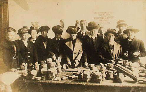 Dames uit de gefortuneerde burgerij komen Belgische vluchtelingen in Middelburg helpen door brood te snijden, 1915. (Zeeuwse Bibliotheek, Beeldbank Zeeland)