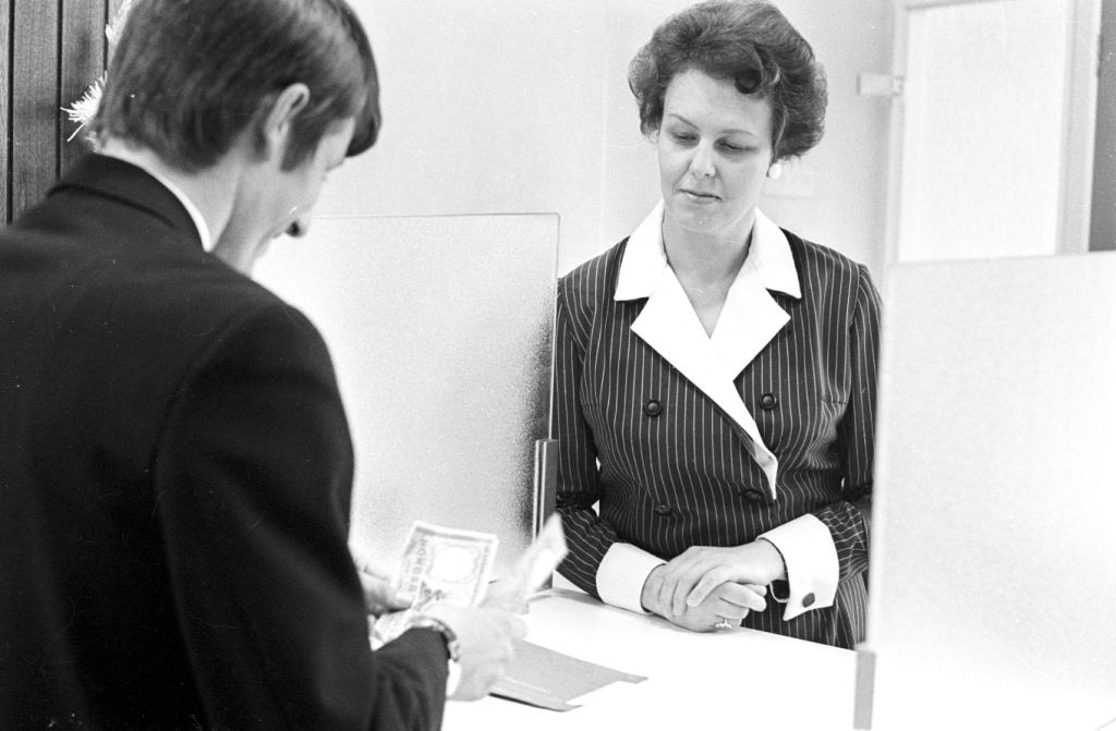 Een bankmedewerkster kijkt toe hoe een klant zijn spaargeld telt, 1972. (Zeeuwse Bibliotheek, Beeldbank Zeeland, foto J. Midavaine)