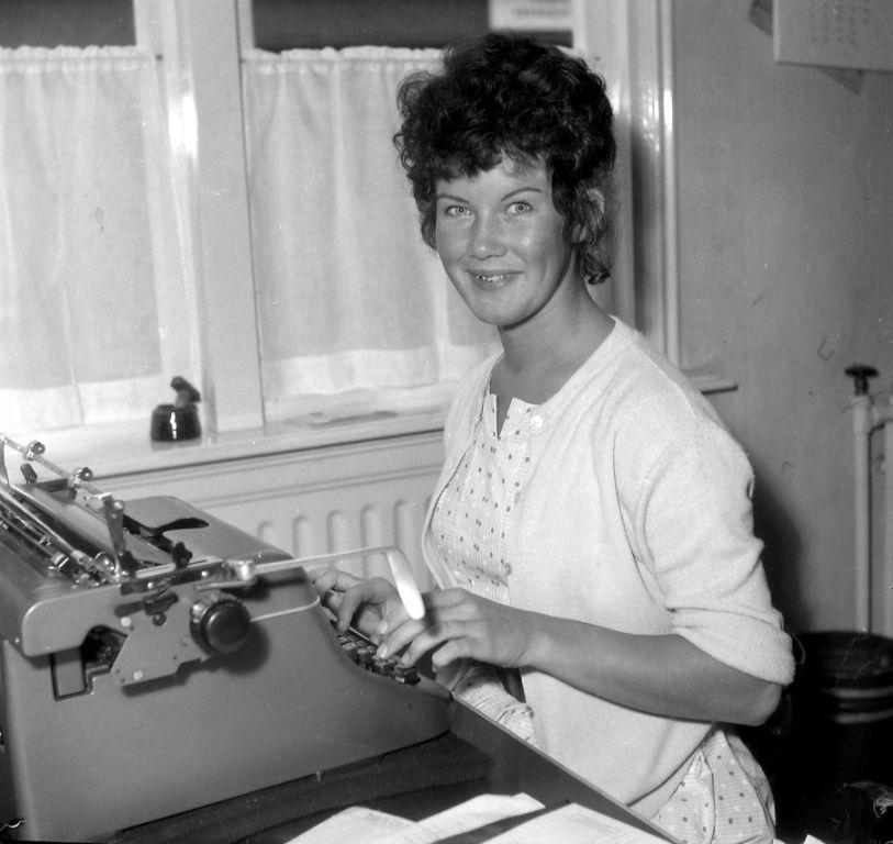 Goese typiste achter een Triumph typemachine. Zij werd gekozen tot fruitfee van het jaarlijkse fruitcorso, 1960. (Zeeuwse Bibliotheek, Beeldbank Zeeland, foto J. Midavaine)
