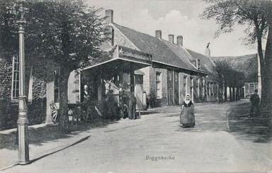 Noordzijde van het Kerkplein, Biggekerke, met links de hoefstal. Prentbriefkaart, circa 1906. (Zeeuwse Bibliotheek, Beeldbank Zeeland)