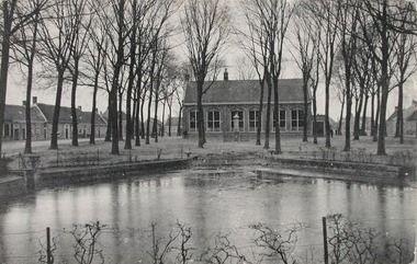 Het Dorpsplein met de openbare lagere school en op de voorgrond de vate. Prentbriefkaart, circa 1910. (Zeeuwse Bibliotheek, Beeldbank Zeeland)
