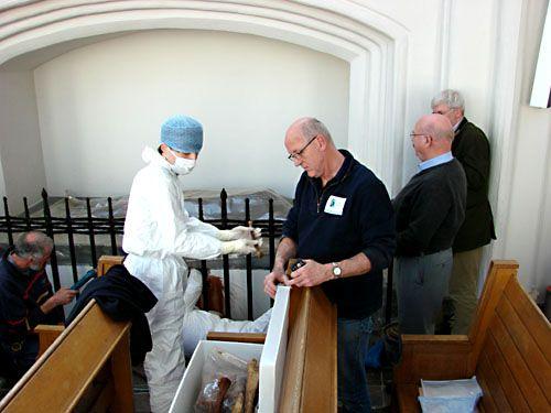 Onderzoek graftombe Koorkerk, 2011. Plaatsen van een los bot in de polytheen doos. De beschermende middelen zijn nodig om te voorkomen dat vreemd DNA-materiaal op de skeletresten terechtkomt.