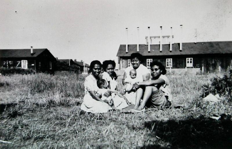 Een Molukse familie voor hun behuizing in kamp Havendorp in Vlissingen, 1958. (Zeeuwse Bibliotheek, Beeldbank Zeeland)