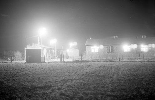 Na de onlusten werd het kamp bij Westkapelle voorzien van prikkeldraad en felle verlichting. (Zeeuwse Bibliotheek, Beeldbank Zeeland, fotoarchief PZC, 17 januari 1957)