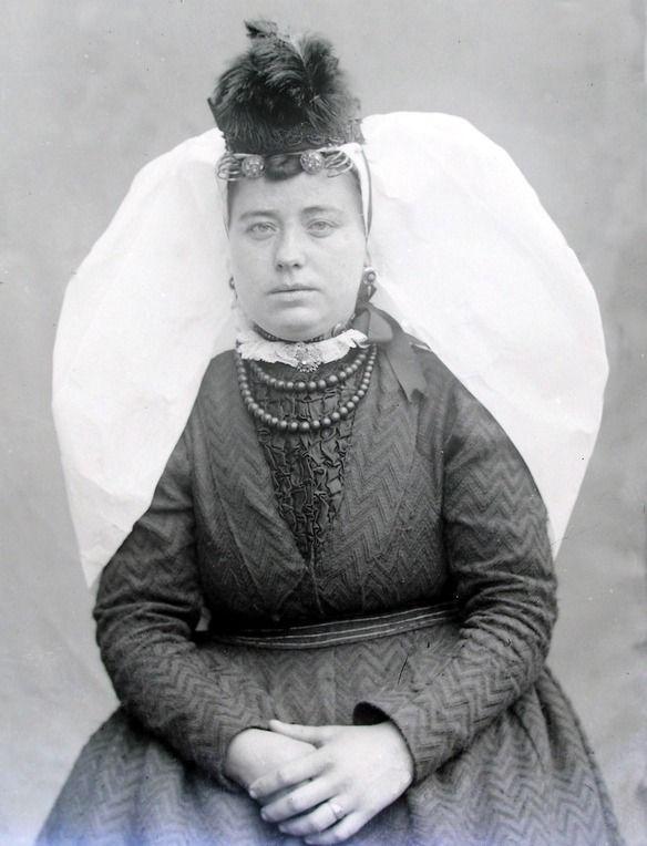Thoolse vrouw in zondags kostuum, met een zogenaamd kipje op de grote sluiermuts. (Zeeuwse Bibliotheek, Beeldbank Zeeland)