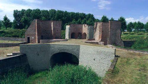 De gerestaureerde ruïne van de Bollewerckpoort in Hulst vanaf de landzijde gezien. Geheel vooraan ligt de tunnel die het havenkanaal overwelft.