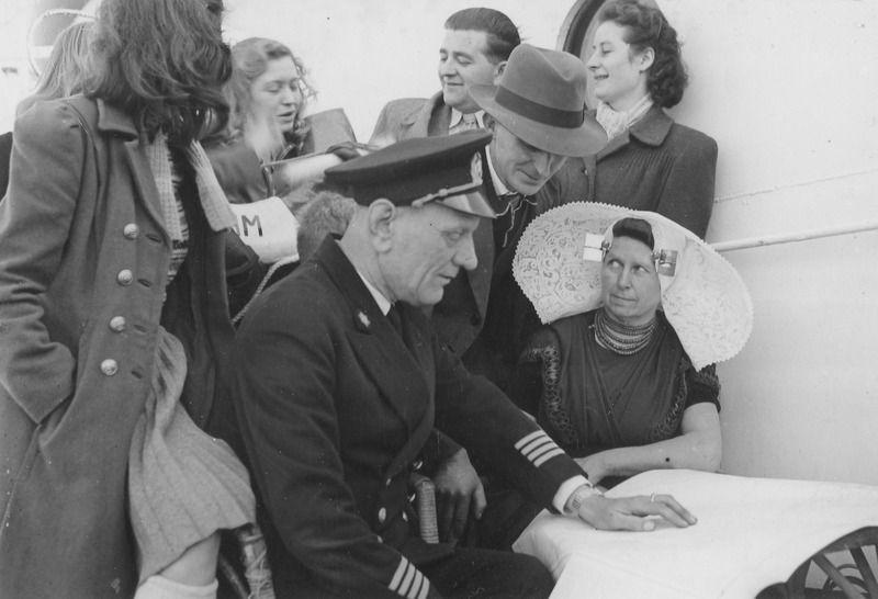 Kapitein G. Visser van de Kota Inten wijst een Zeeuwse familie de vaarroute naar Canada. Zij behoren tot de eerste groep van 700 Zeeuwen die naar dit land emigreren. Foto van 12 maart 1948. (Zeeuwse Bibliotheek, Beeldbank Zeeland)