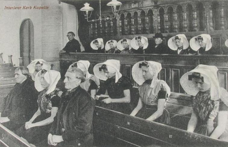 De Afgescheidenen voelden zich niet langer thuis en verlieten na de Hervormde Kerk ook Nederland zelf. Kerkgangers in de kerk van Kapelle op een prentbriefkaart van rond 1920. (Zeeuwse Bibliotheek, Beeldbank Zeeland)