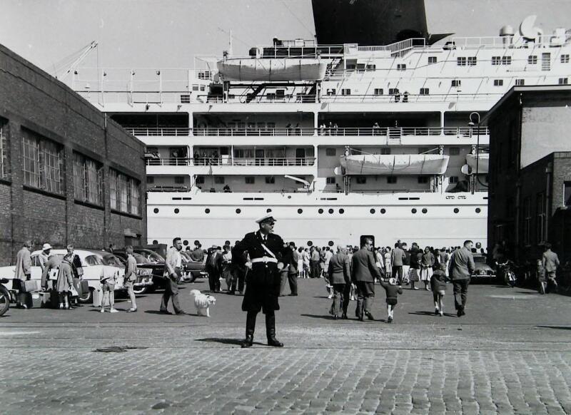 De Willem Ruys ligt in de buitenhaven van Vlissingen. Emigranten gaan aan boord voor de overtocht naar Canada, 2 februari 1958. (Zeeuwse Bibliotheek, Beeldbank Zeeland)