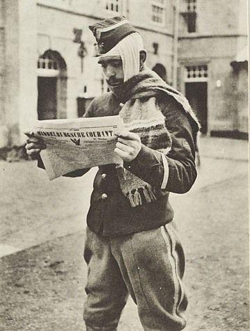Gewonde Belgische militair leest de Middelburgsche Courant bij het ziekenhuis aan de Achtergracht in Middelburg, prentbriefkaart, 1914-1918. (Zeeuws Archief, coll. Zeeuws Genootschap, Zelandia Illustrata)
