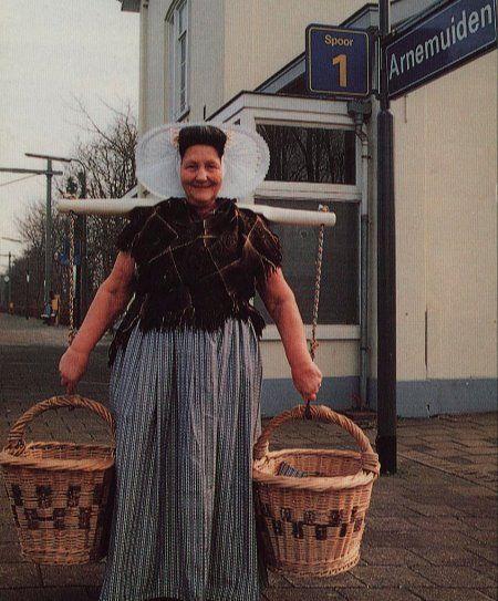 Mevrouw Van Belzen in hedendaagse Arnemuidse dracht met een juk met twee emmers, op het perron van station Arnemuiden, circa 1992 (Zeeuws Archief, KZGW, Zelandia Illustrata).