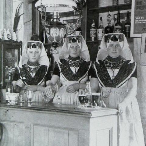 Vrouwen achter de toog in Ovezande in de katholieke vrouwendracht van Zuid-Beveland, 1924 (ZB, Beeldbank Zeeland).