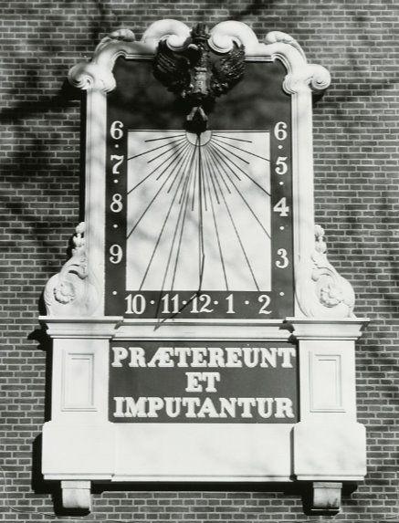 De verticale (vlakke) zonnewijzer, nu hangend aan de gevel van het stadhuis in Middelburg, met een verticale 12-uurlijn, maar links en rechts asymetrisch uurlijnenpatroon. De foto is in 1994 genomen toen de zonnewijzer nog aan de gevel hing van de streekschool aan de Zuidsingel (Zeeuws Archief, HTAM, foto J. van der Vossen).