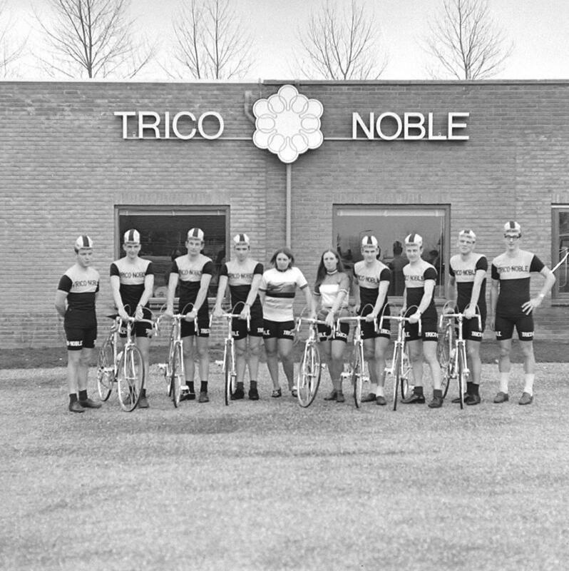 De wielerploeg van Trico Noble poseert omstreeks 1968 voor het fabrieksgebouw in Aardenburg. (Zeeuwse Bibliotheek, Beeldbank Zeeland, foto O. de Milliano)