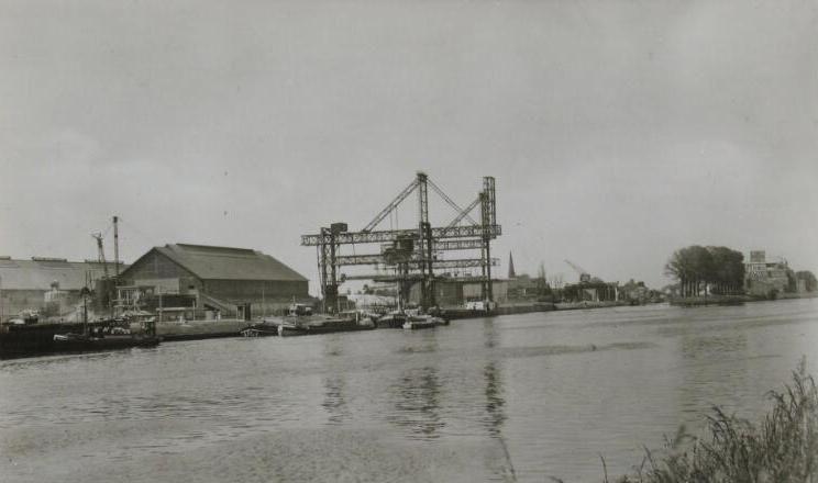 De fosfaatfabriek met laad- en loskranen aan het kanaal omstreeks 1950. (Zeeuwse Bibliotheek, Beeldbank Zeeland)