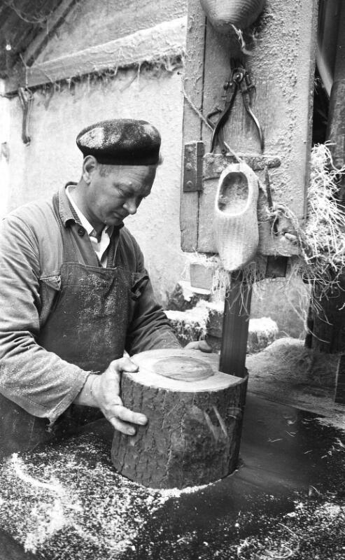 Klompenmaker in Kapellebrug zaagt de blokken hout in wigvormige stukken. (ZB, Beeldbank Zeeland, coll. Dagblad De Stem, foto C. de Boer)