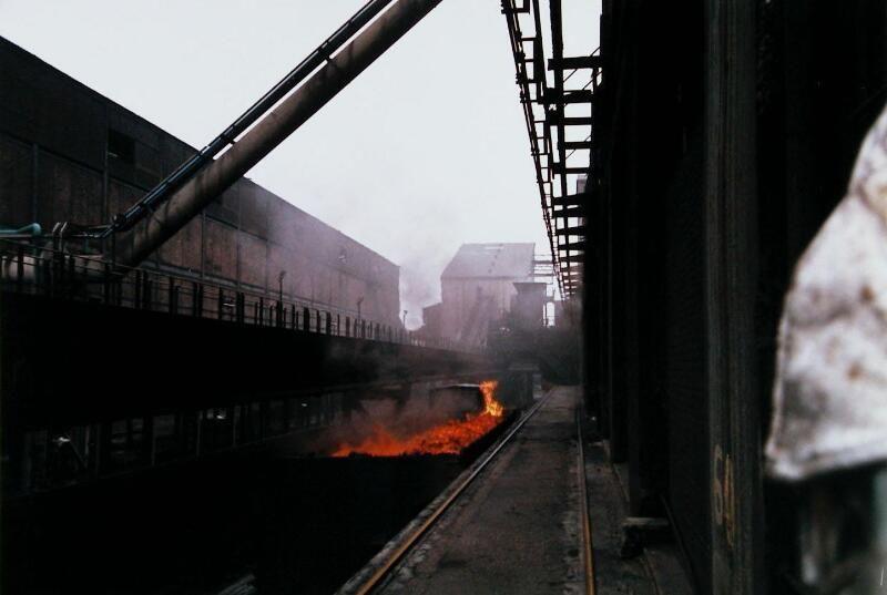 Bluswagen met cokes op weg naar de blustoren. Foto uit 1999 net voor de sluiting van de fabriek. (Zeeuwse Bibliotheek, Beeldbank Zeeland, foto P. Smit)