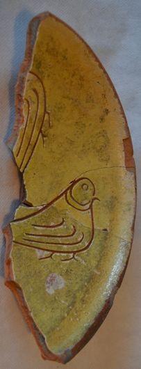 Fragmenten van een voetschaal van rood aardewerk met gele slib. In de spiegel is een versiering van vogels ingekrast. Datering tweede helft vijftiende eeuw. (Erfgoed Zeeland, Beeldbank Archeologie)