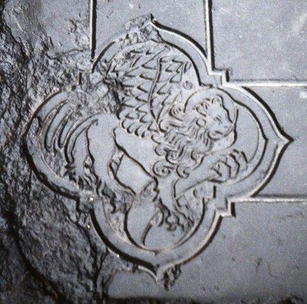 Afbeelding van het symbool van de evangelist Marcus, de leeuw, linksonder in het randschrift van de grote grafsteen uit het middenschip van de kerk van Nieuwerkerke. (Beeldbank SCEZ)