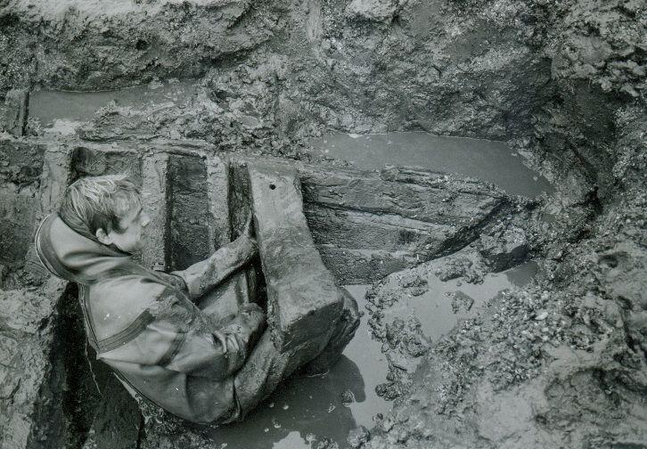 Opgraving van het voorschip van het scheepje van Nieuwlande. De los gevonden zware balk wordt in de oorspronkelijke positie gehouden. (Rijksdienst voor het Cultureel Erfgoed, Amersfoort)