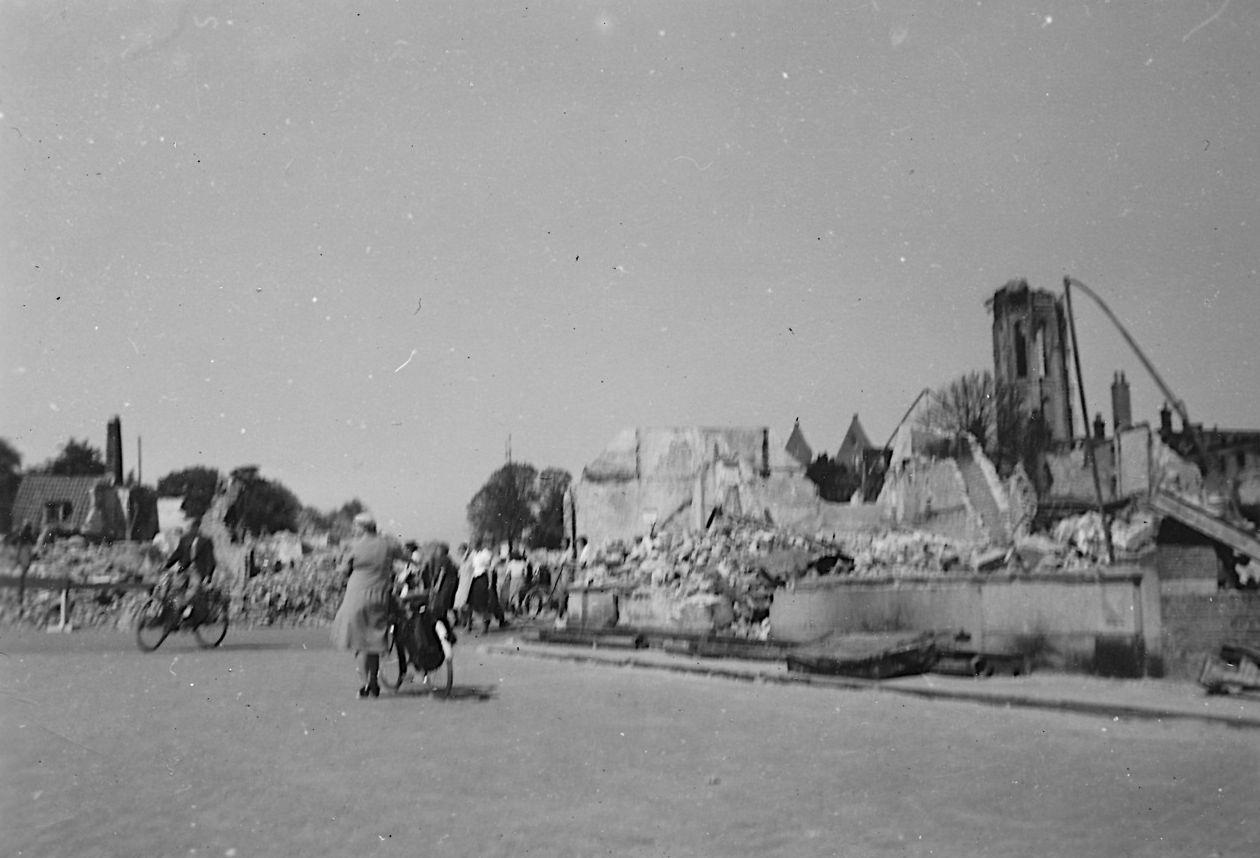Voorbijgangers nemen de schade op na de brand in Middelburg in mei 1940. (Particuliere collectie)