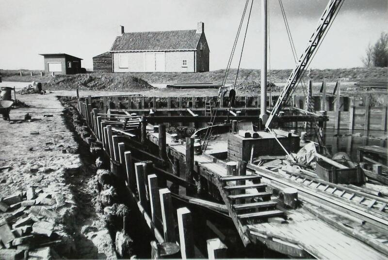 Aanbrengen van een nieuwe loswal in Geersdijk, 1976. Op de achtergrond de weegbrug. (ZB, Beeldbank Zeeland, foto W. Helm)